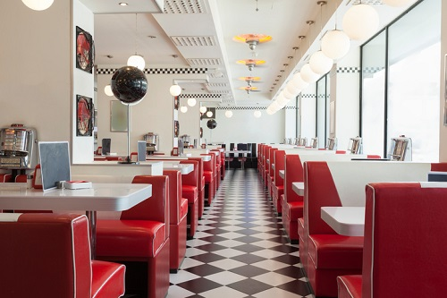 inside a diner style restaurant with red and white tables